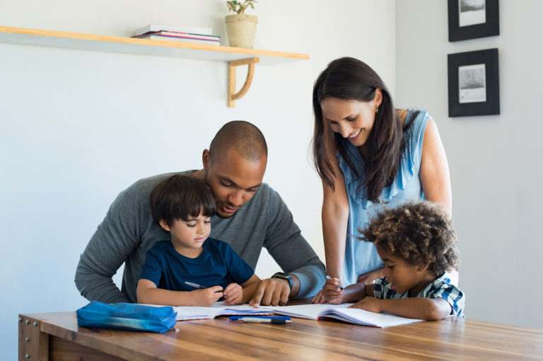 Multiethnic parents helping children with their homework at home