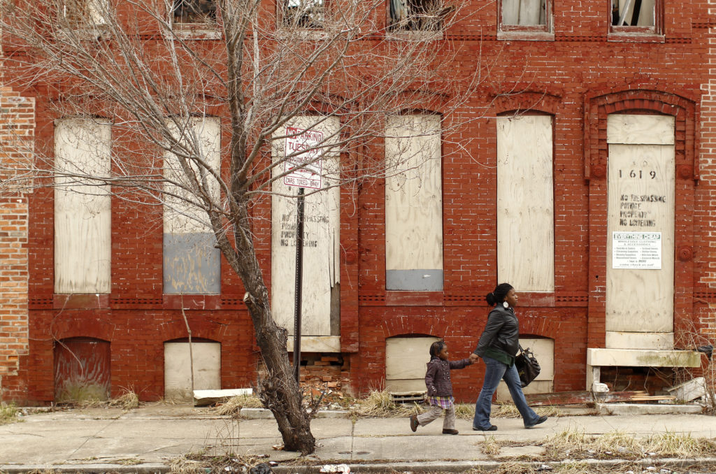 A woman and child walk past a dilapidated building in a run-down neighborhood of Baltimore