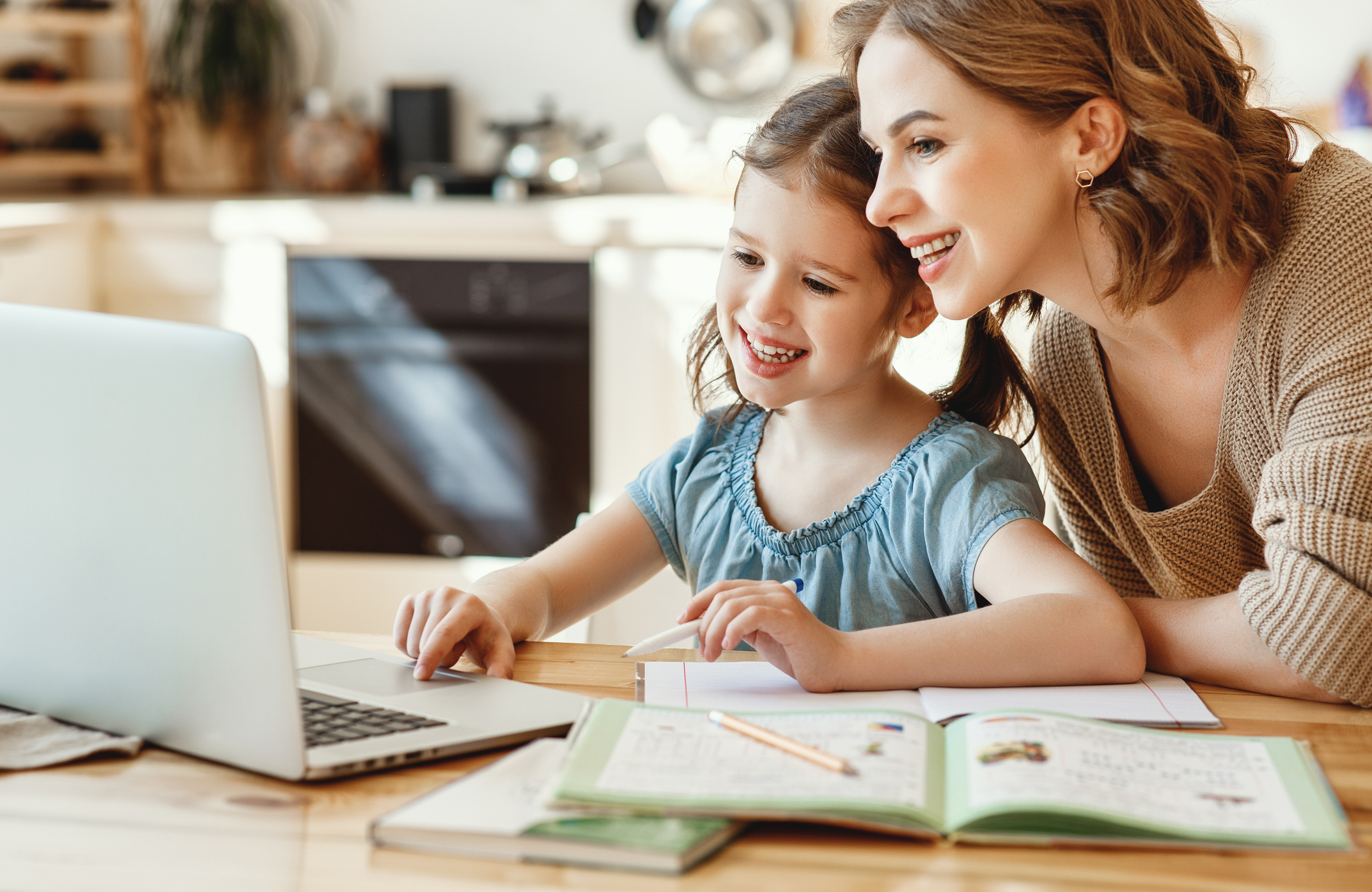 Happy girl with mother studying online at home